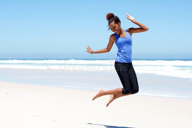 Mujer deportiva que salta en la playa imagen de archivo