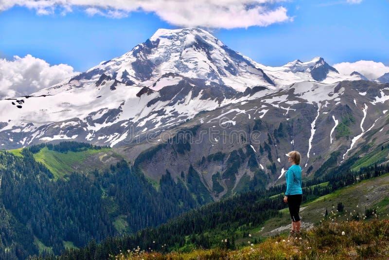 Mujer deportiva que se relaja en prados alpinos y que disfruta de la vista escénica del volcán cubierta con los glaciares y la ni fotografía de archivo libre de regalías