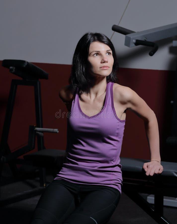 Mujer deportiva que se sienta en el piso en el centro de aptitud imagen de archivo libre de regalías