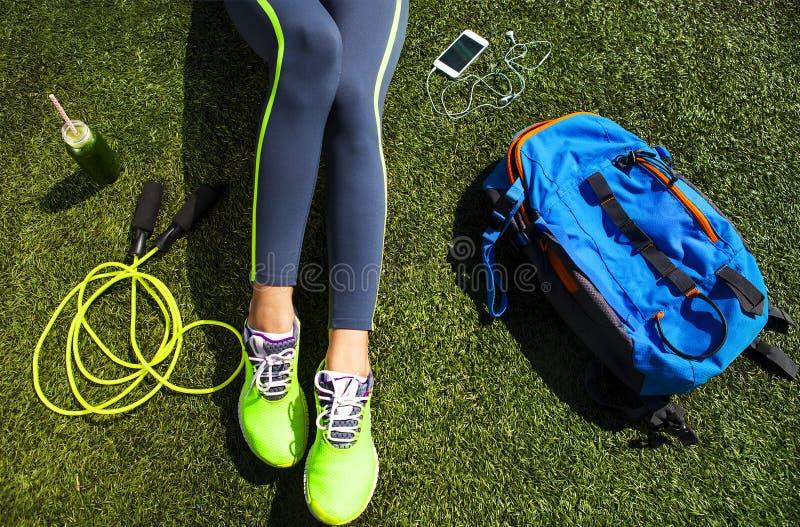 Mujer deportiva que se sienta en la hierba verde foto de archivo libre de regalías