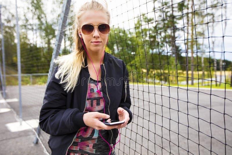 Mujer deportiva que sostiene el teléfono móvil mientras que música que escucha por la cerca imagenes de archivo