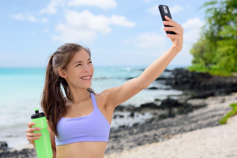 Mujer deportiva sonriente que toma Selfie en la playa imágenes de archivo libres de regalías