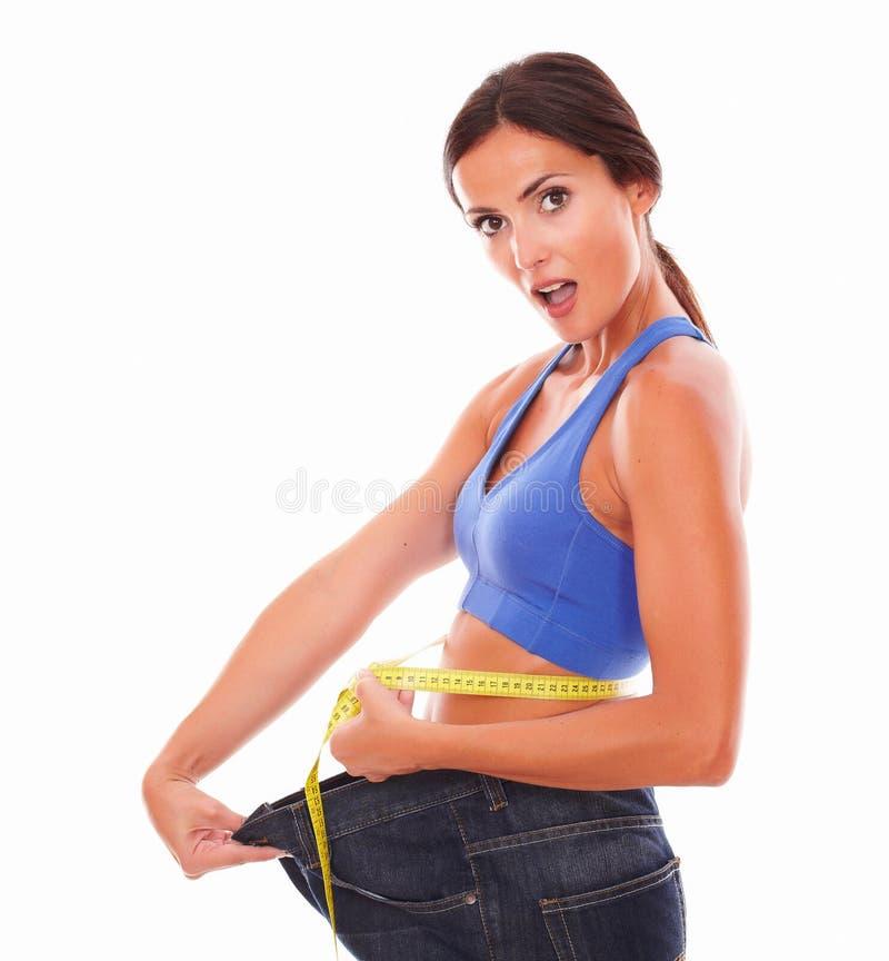 Mujer deportiva sorprendida que mide su cintura imagen de archivo