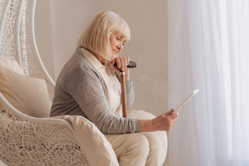 Mujer deprimida cambiante que sostiene una foto foto de archivo