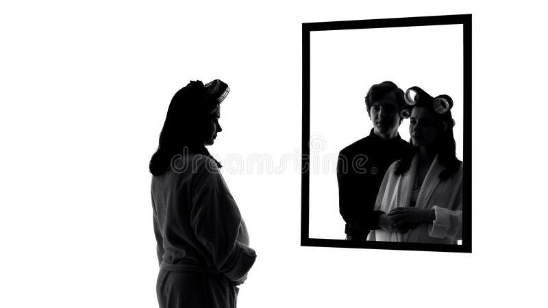 Mujer deprimida embarazada que mira en el espejo solo, imaginándose al marido el abrazar de ella fotos de archivo