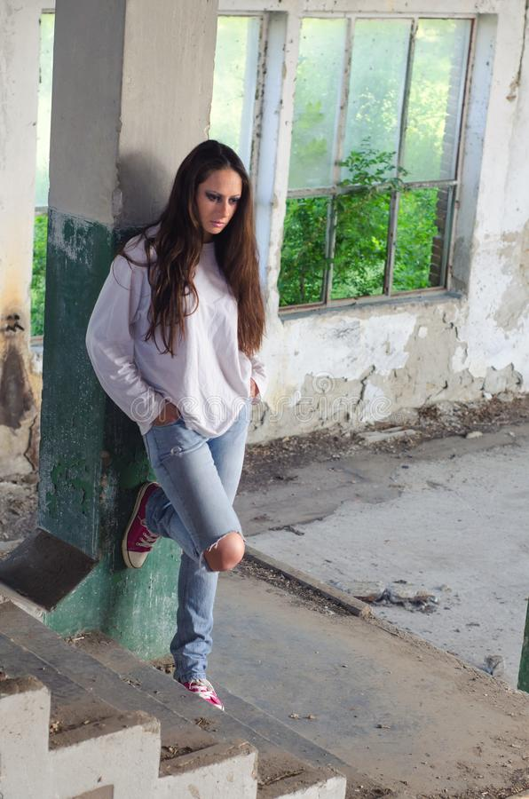 Mujer deprimida en el edificio abandonado imagenes de archivo