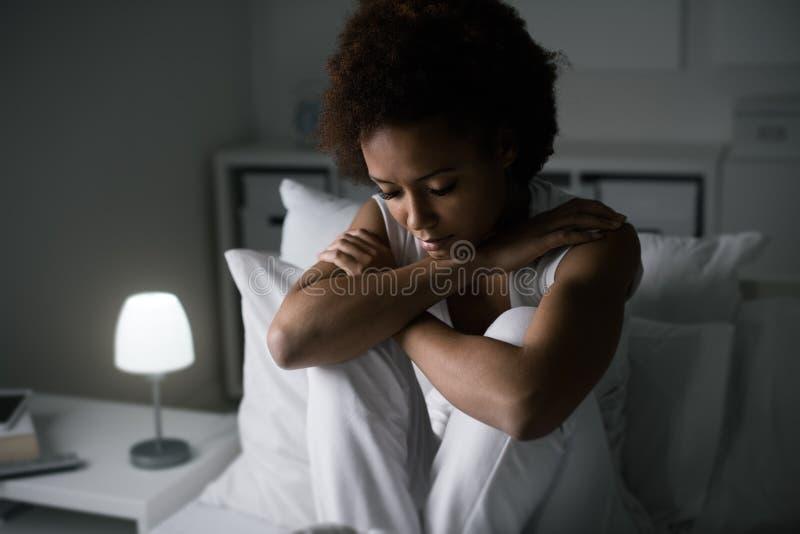 Mujer deprimida en su cama imagen de archivo