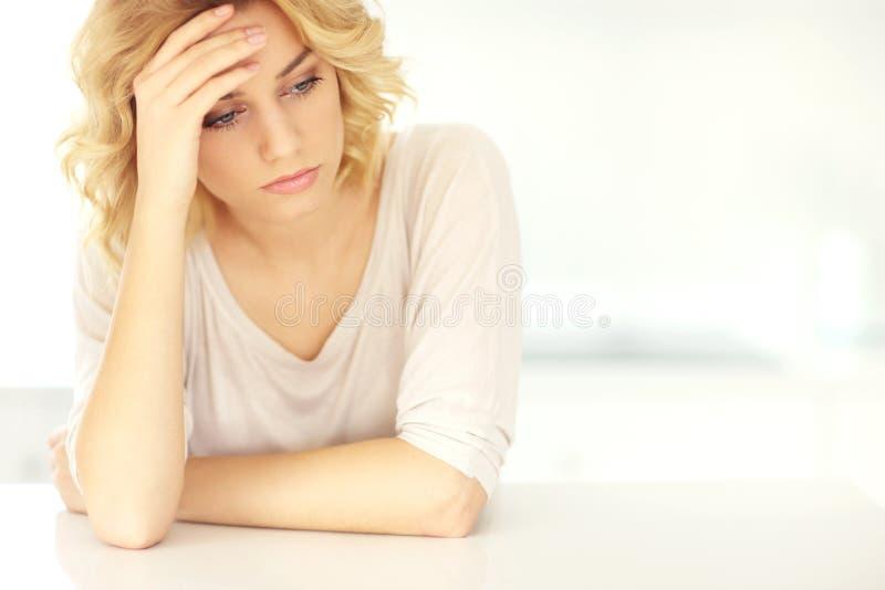 Mujer deprimida joven en casa foto de archivo