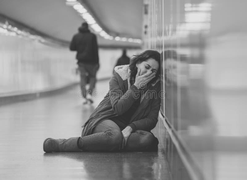 Mujer deprimida joven que llora en la tierra en el metro del subterráneo foto de archivo