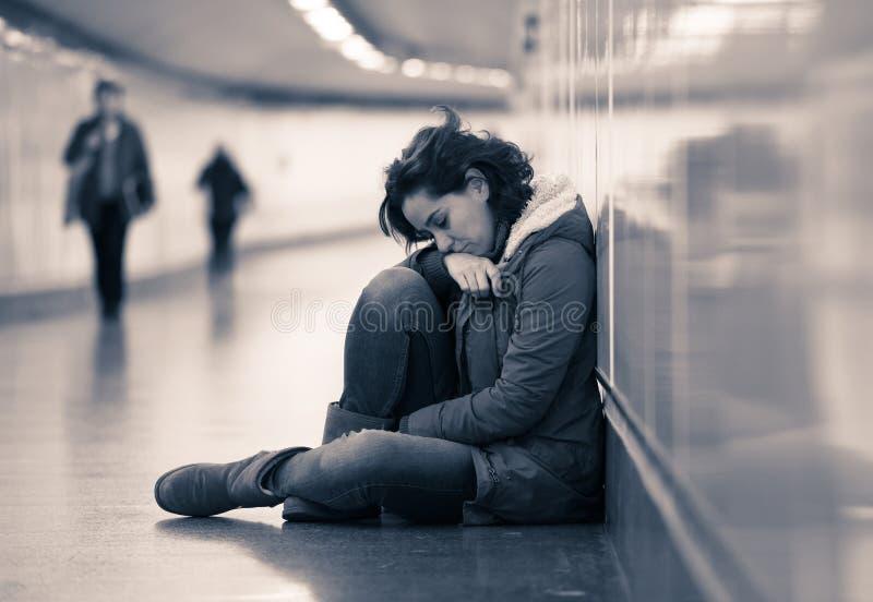 Mujer deprimida joven que llora en la tierra en el metro del subterr?neo imagen de archivo