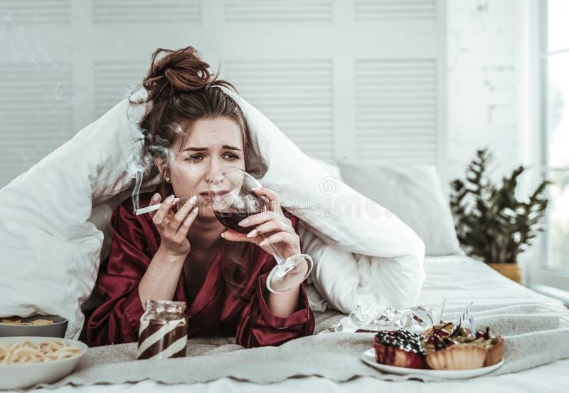 Mujer deprimida que fuma en la cama y el vino de consumición foto de archivo libre de regalías
