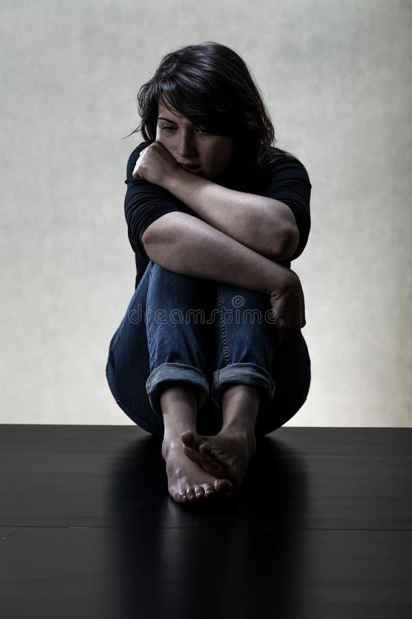 Mujer deprimida que se sienta en el suelo imagen de archivo