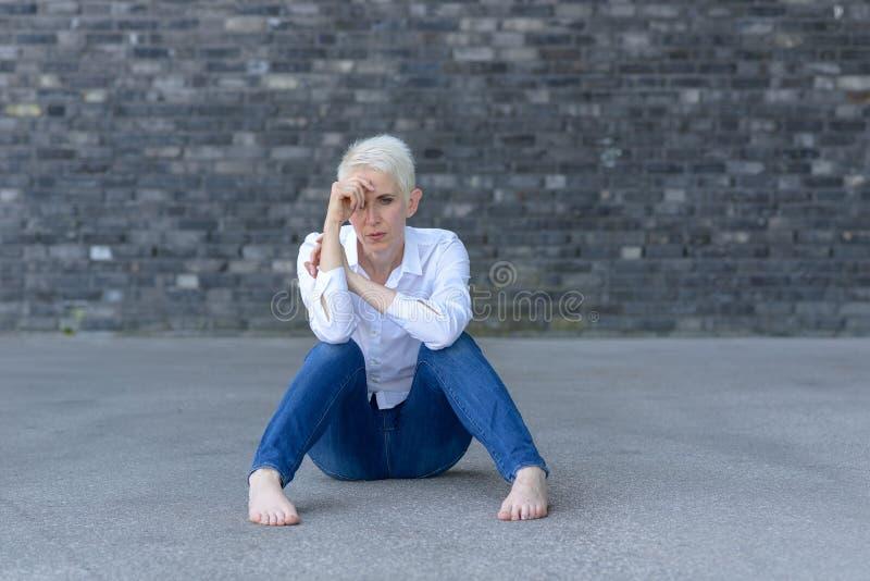 Mujer deprimida que se sienta en la tierra imagen de archivo