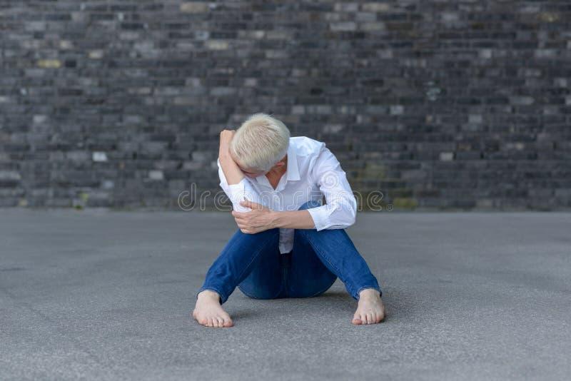Mujer deprimida que se sienta en la tierra fotos de archivo