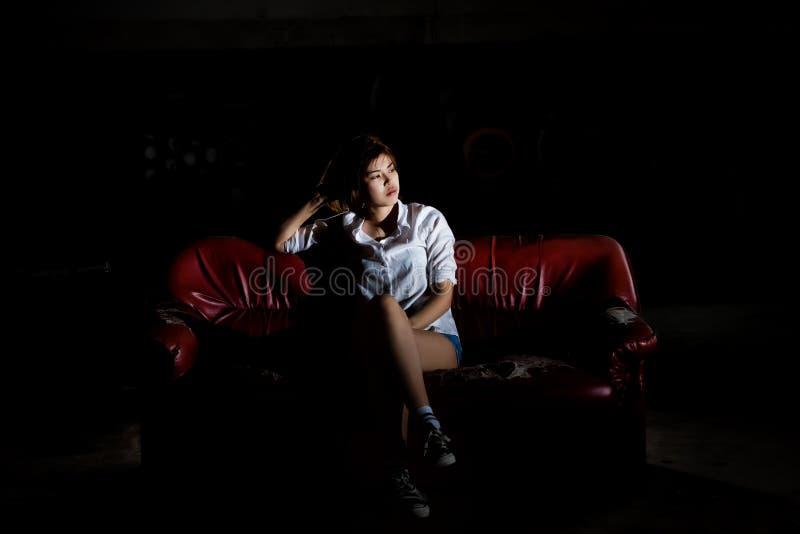 Mujer deprimida sola infeliz que se sienta en el viejos sofá y contempl fotografía de archivo