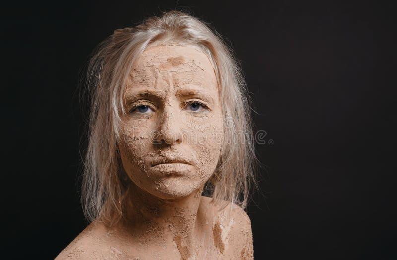 Mujer desaliñada cubierta en fango agrietado seco imagen de archivo