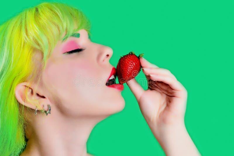 Mujer descamisada joven hermosa que sostiene la fresa en su mano y que la prueba mientras que se opone a fondo verde fotos de archivo libres de regalías