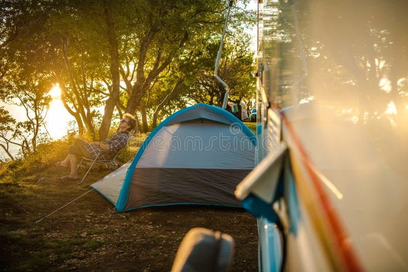 Mujer descansando en un camping cerca de RV imagen de archivo libre de regalías