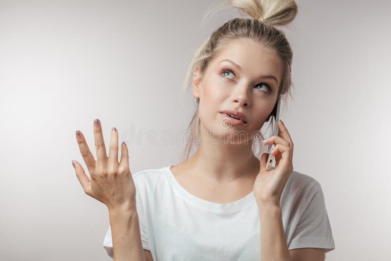 Mujer desconcertada confusa que sostiene su teléfono elegante Emociones humanas, lenguaje corporal imágenes de archivo libres de regalías