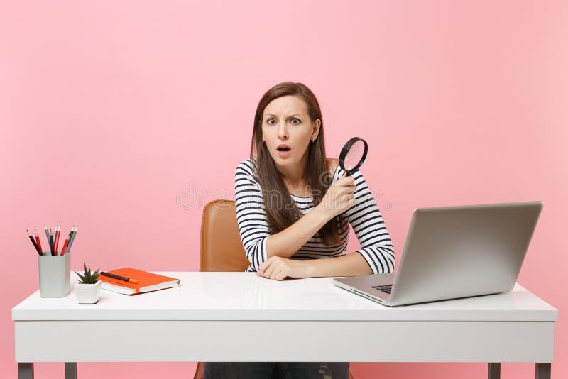 Mujer desconcertada Scared en el funcionamiento que se sienta de la lupa de la tenencia de la perplejidad en proyecto en el escri foto de archivo libre de regalías