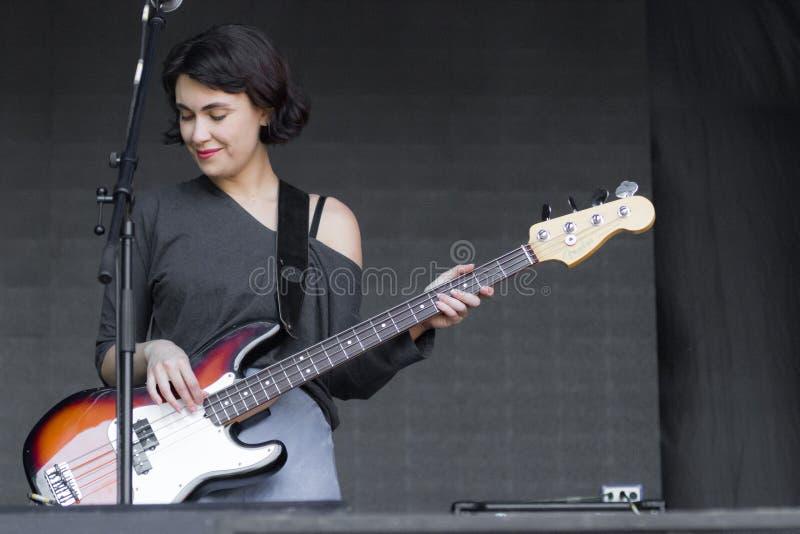 Mujer desconocida con la guitarra baja acústica en etapa fotografía de archivo libre de regalías
