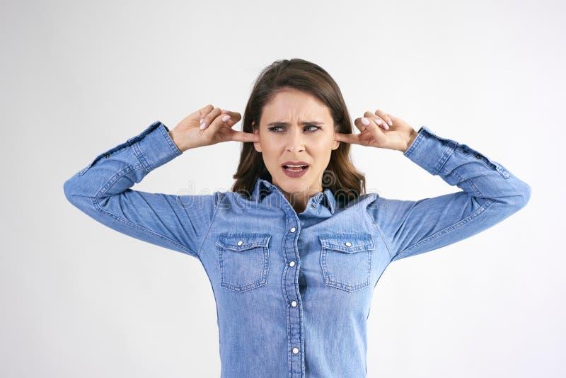Mujer descontentada que cubre sus oídos imagenes de archivo