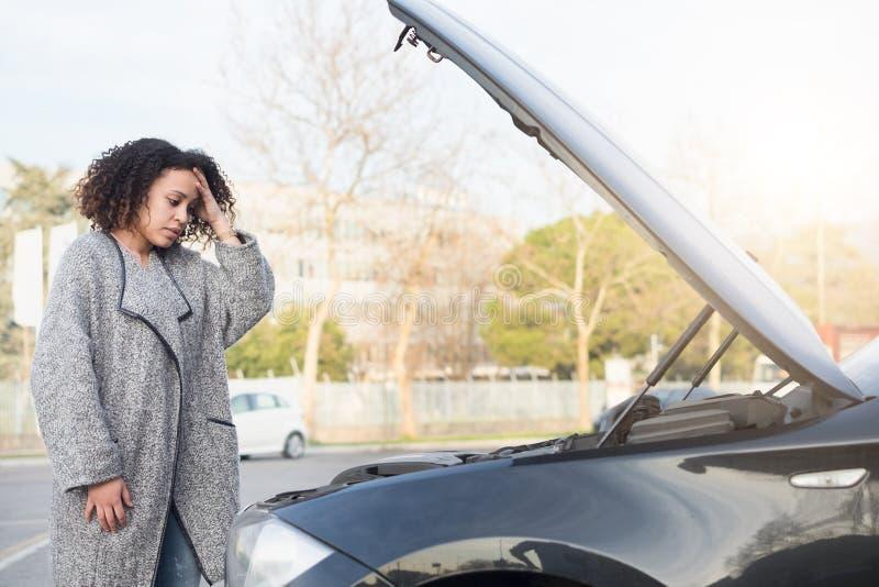 Mujer desesperada después de comprobar el motor roto coche imagenes de archivo