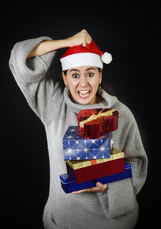 Mujer desesperada divertida en el sombrero de Santa Christmas en la tensión sobre el griterío que hace compras de los regalos y d foto de archivo