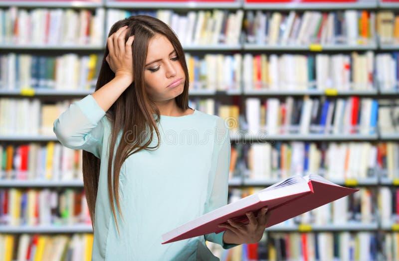 Mujer desesperada que mira su libro fotografía de archivo libre de regalías
