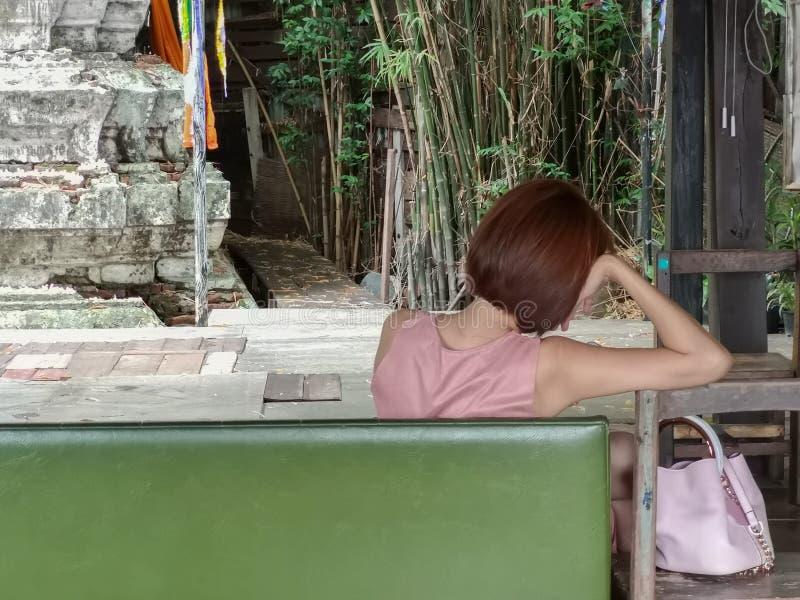 Mujer desesperada sola con la sentada sola de pensamiento del vestido rosado y del bolso rosado en un banco verde imágenes de archivo libres de regalías