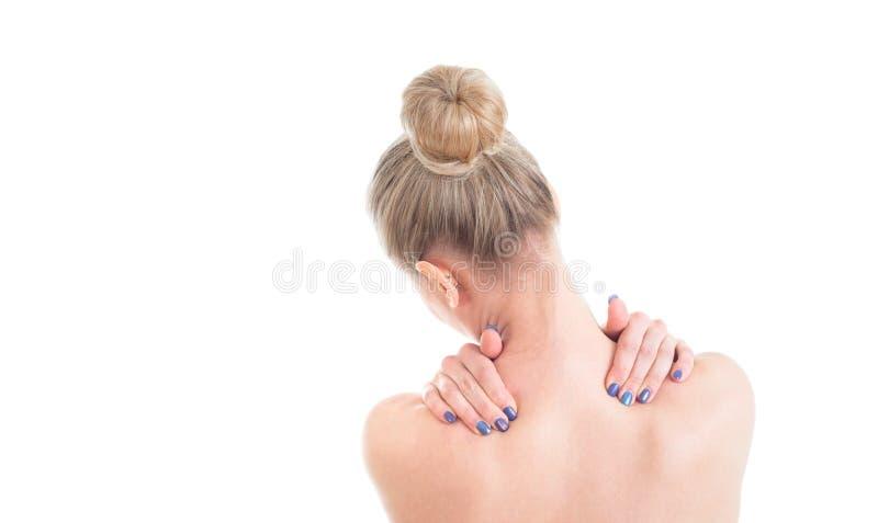 Mujer desnuda con dolor de cuello Visión posterior Estudio tirado en la parte posterior del blanco imagenes de archivo