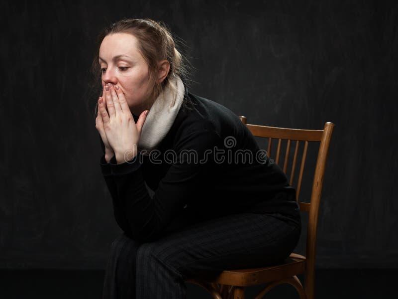 Mujer desorientada triste joven que se sienta en la silla imagenes de archivo