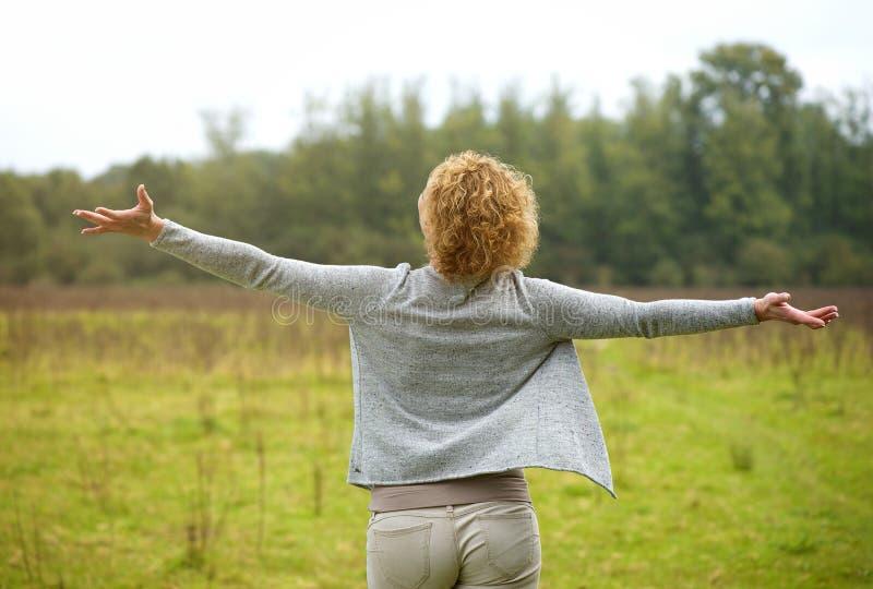 Mujer despreocupada con la extensión de los brazos abierta al aire libre fotos de archivo libres de regalías