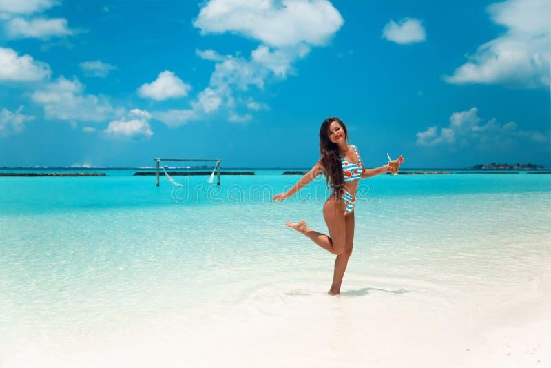 Mujer despreocupada del bikini en la playa tropical Muchacha delgada bonita con el coctail que goza en la isla exótica en el oc fotos de archivo libres de regalías