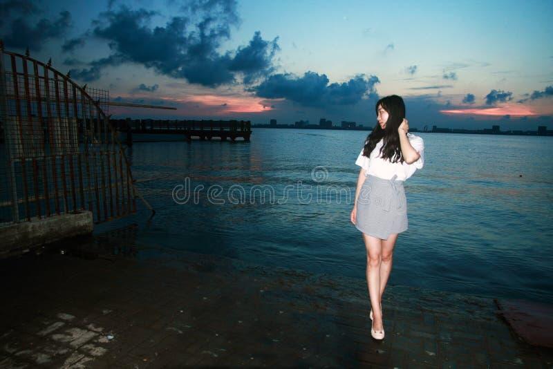 Mujer despreocupada en la puesta del sol por el lago Dishui en Shangai, concepto vivo sano, felicidad pura y la libertad fotos de archivo libres de regalías