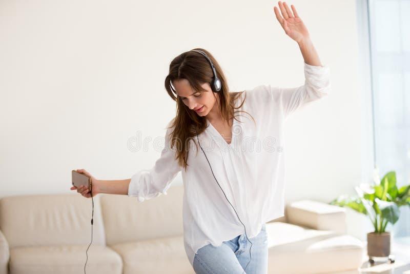 Mujer despreocupada en los auriculares que bailan a la música que juega en smartph fotos de archivo