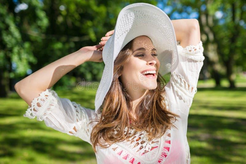 Mujer despreocupada hermosa que aumenta las manos sobre la risa de la cabeza imágenes de archivo libres de regalías