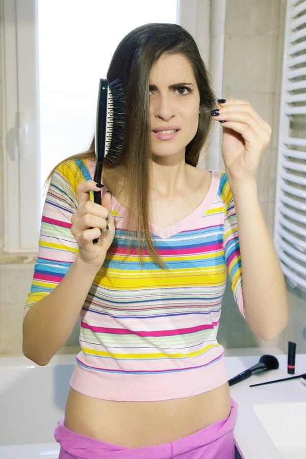 Mujer después de cepillar el pelo largo desesperado sobre la pérdida de pelo que mira la cámara imagen de archivo