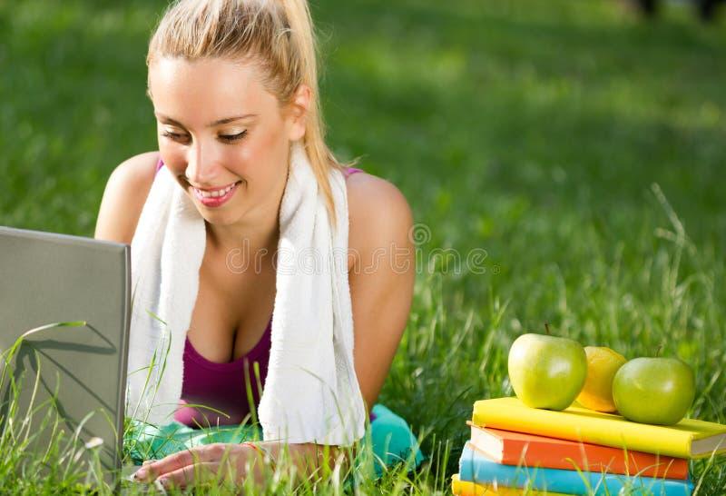 Mujer después de ejercitar en el parque que descansa y que usa el ordenador portátil fotos de archivo libres de regalías