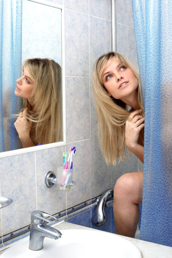 Mujer después de la ducha en cuarto de baño fotos de archivo
