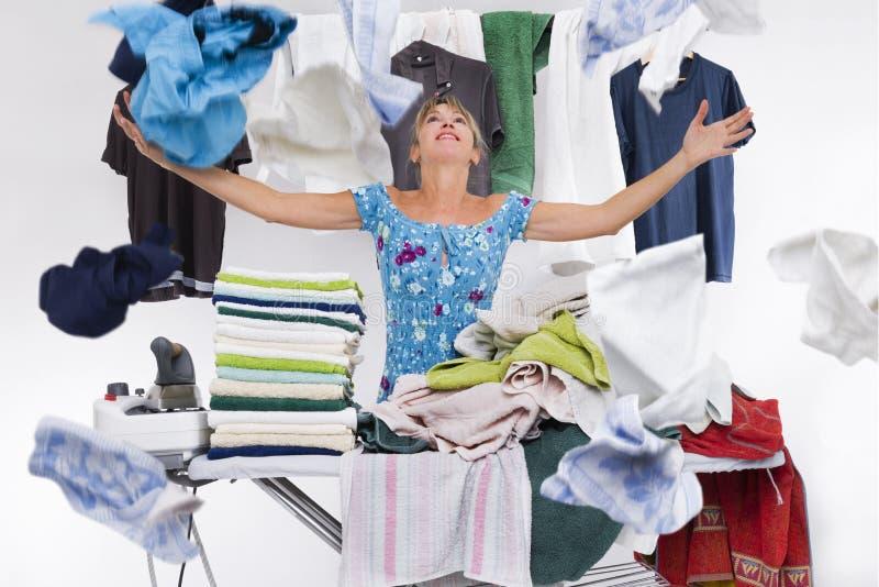 Mujer detrás de la ropa superior de los lanzamientos de un tablero que plancha apenas planchada imagen de archivo