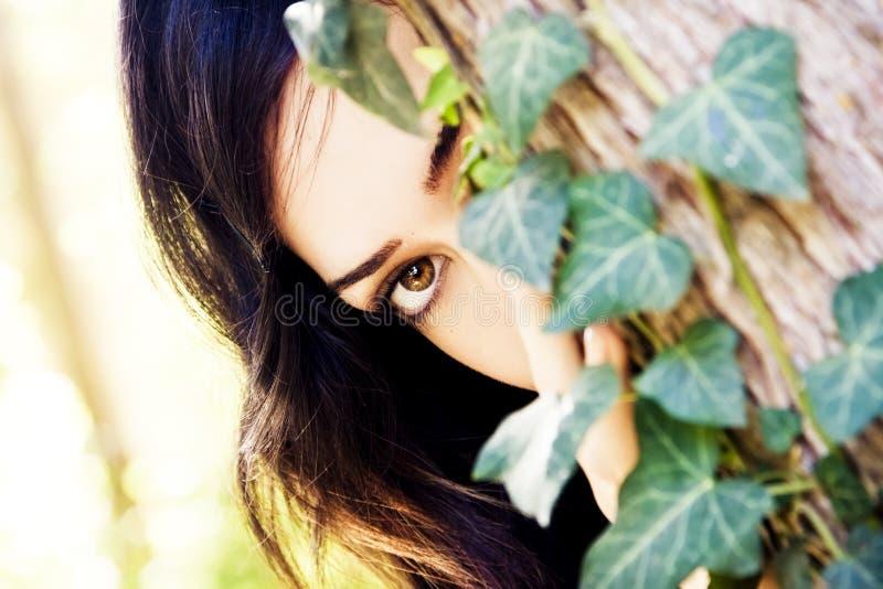 Mujer detrás de las hojas imagenes de archivo