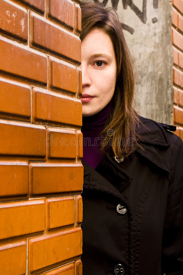 Mujer detrás del brickwall imagen de archivo libre de regalías