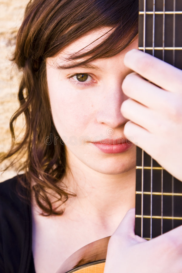Mujer detrás del fretboard de la guitarra imagenes de archivo