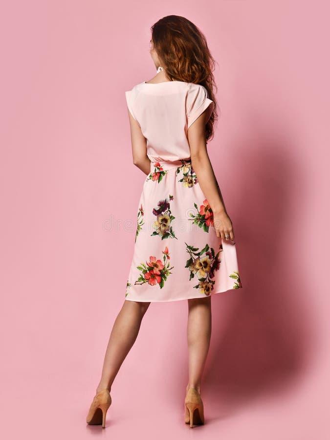Mujer detrás en una blusa y una falda mullida que presentan en el estudio en un fondo rosado para hacer frente a la primavera y a fotos de archivo