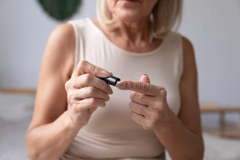 Mujer diabética madura sosteniendo con un medidor de glucosa en sangre en el dormitorio foto de archivo
