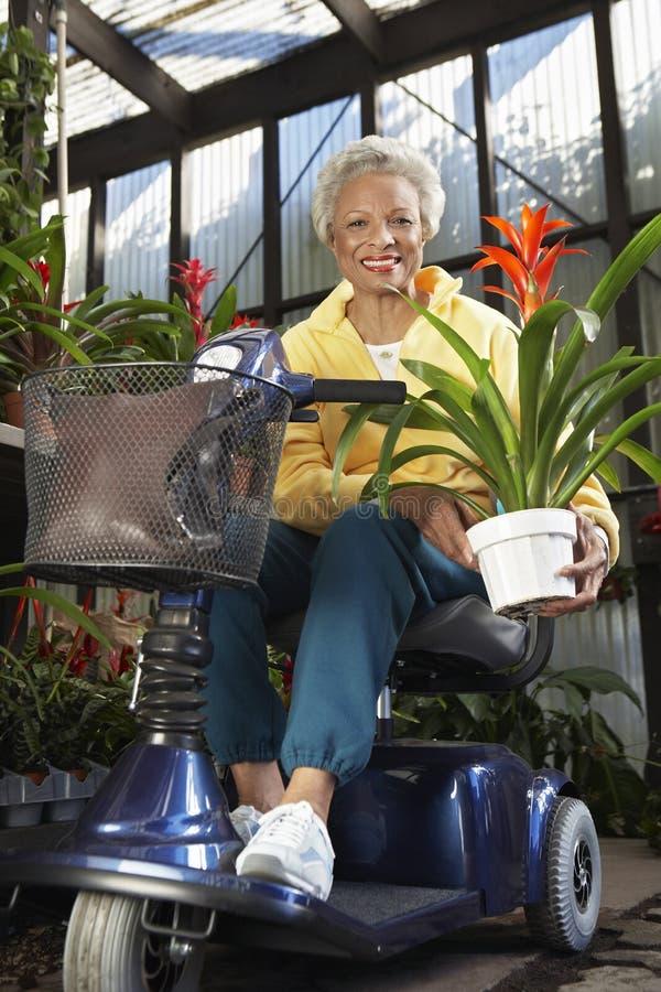 Mujer discapacitada en la vespa de motor con la planta en el jardín botánico fotografía de archivo libre de regalías