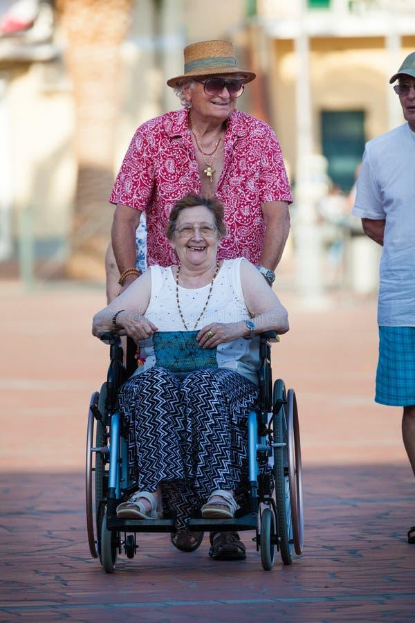 Mujer discapacitada en una silla de ruedas Amor de un par mayor imagen de archivo libre de regalías