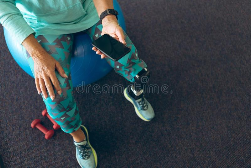 Mujer discapacitada usando el teléfono móvil en centro de aptitud fotografía de archivo libre de regalías
