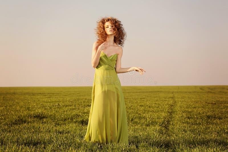 Mujer diseñada hermosa con un vestido del verde largo en campos imágenes de archivo libres de regalías